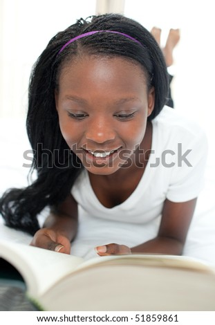 Concentrated student doing her homework lying on her bed - stock photo