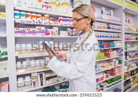 Concentrated student using tablet pc in the pharmacy - stock photo