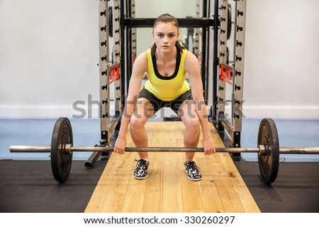 Concentrated woman about to lift a barbell and weights at the gym - stock photo