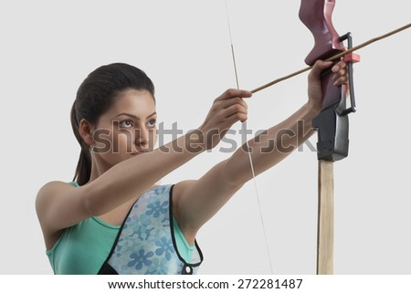 Concentrated woman practicing archery against gray background - stock photo