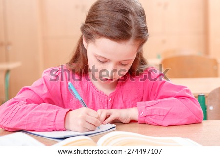 Concentrated writing. Little girl writing at desk in her copy during classes - stock photo