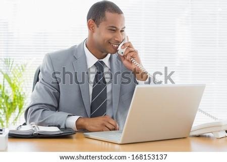 Concentrated young businessman using laptop and phone at the office desk - stock photo