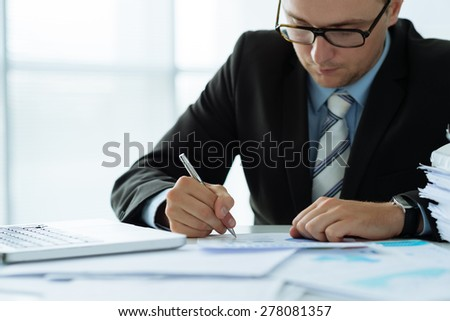 Concentrated young businessman working with financial document in the office - stock photo