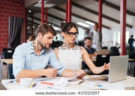 Concentrated young businesspeople using laptop and working together in office - stock photo