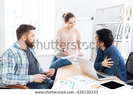 Concentrated young businesspeople working and making new project in office together  - stock photo