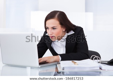Concentrated young businesswoman using laptop at desk in office - stock photo