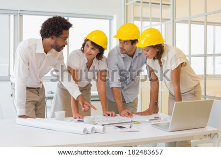 Concentrated young colleagues working on blueprints at the office - stock photo