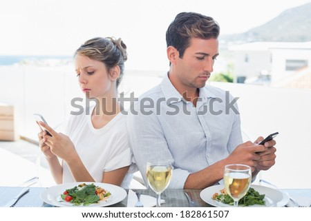 Concentrated young couple text messaging at food table - stock photo