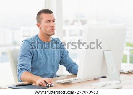 Concentrated young creative businessman working on the computer - stock photo