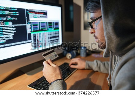 Concentrated young hacker in glasses stealing money from different credit cards sitting in dark room - stock photo