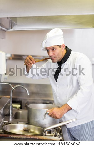 Concentrated young male cook tasting food in the kitchen - stock photo
