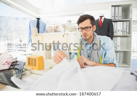 Concentrated young male tailor sewing in workshop - stock photo