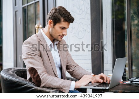 Concentrated young man sitting and using laptop in outdoor cafe - stock photo