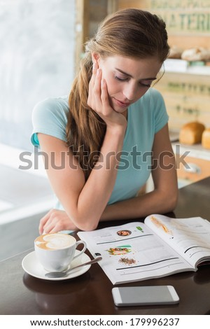 Concentrated young woman with coffee cup reading magazine at counter in the coffee shop - stock photo