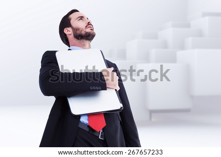 Concentrating businessman in suit holding laptop against abstract white design - stock photo