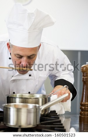 Concentrating head chef tasting sauce with wooden spoon in professional kitchen - stock photo
