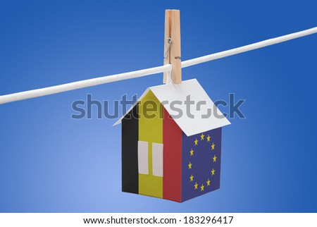 concept - Belgian and EU flag painted on a paper house hanging on a rope - stock photo