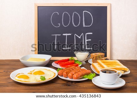 concept breakfast with handwritten text good time on blackboard with setting food products over wooden background - stock photo