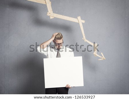 Concept: Business failure. Disappointed businessman presenting white empty signboard with space for text in front of business graph with negative trend, isolated on grey background. - stock photo