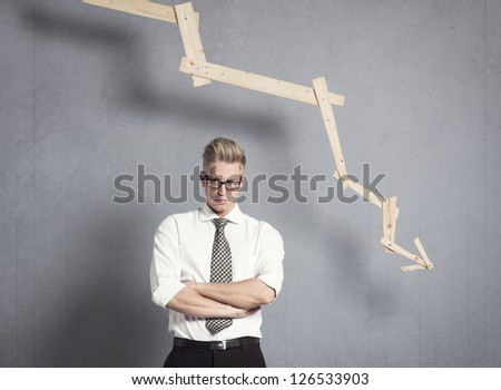 Concept: Business failure. Miffed irritated businessman in front of business graph pointing down, isolated on grey background. - stock photo