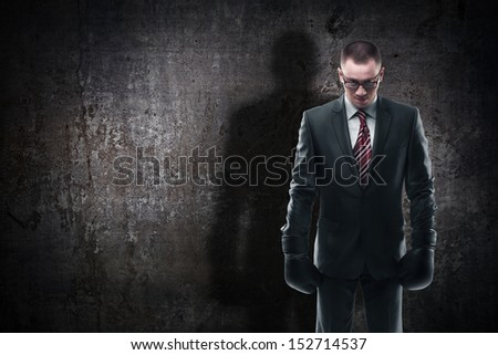 Concept businessman with boxing gloves and shadow standing on grounge background  - stock photo