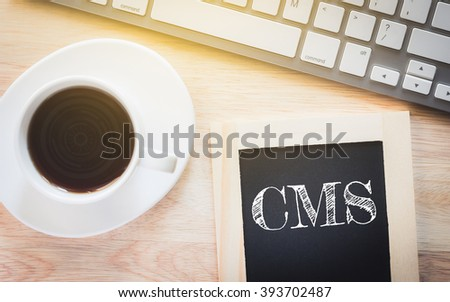 Concept CMS message on wood boards. A keyboard and a glass coffee table.Vintage tone. - stock photo