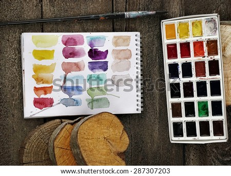 concept composition of paints and notepad on the dark wooden background - stock photo