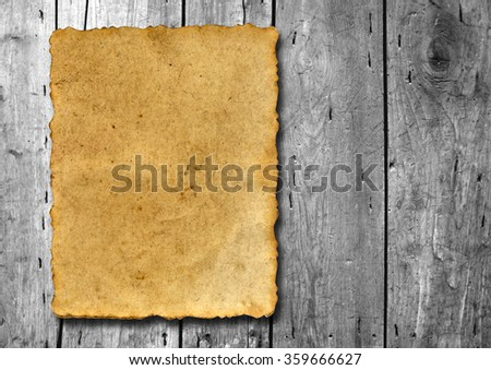 Concept conceptual old vintage brown damaged paper texture over a wood background, metaphor for aged, retro, wooden, dirty, textured, manuscript, antique, parchment, book, ancient, weathered or grungy - stock photo