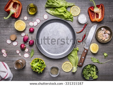 concept cooking vegetarian food ingredients laid out around the pan with a knife and spices space for text on rustic wooden background top view - stock photo