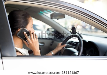 Concept danger driving Woman using cell phone while driving car - stock photo