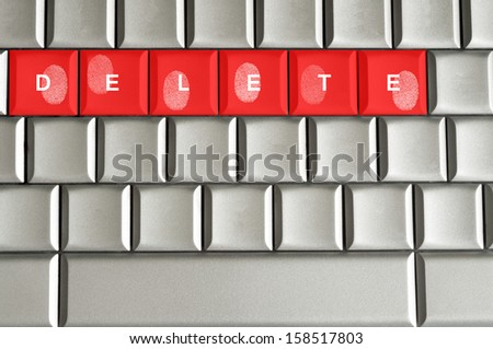 Concept delete spelled on metallic keyboard with fingerprints overlaid - stock photo