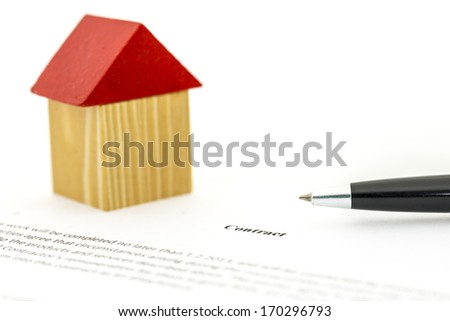 Concept depicting the buying or selling of a house with a ballpoint pen and wooden model of a home standing on a written contract which could be either a deed of sale, lease or insurance agreement - stock photo