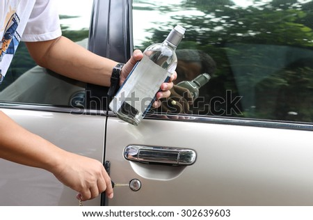 Concept drunk man holding bottle of whiskey try to drive a car social problem - stock photo