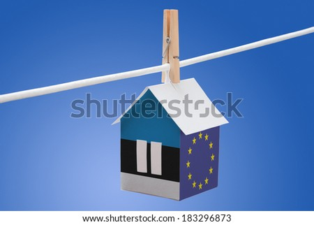 concept - Estonia and EU flag painted on a paper house hanging on a rope - stock photo