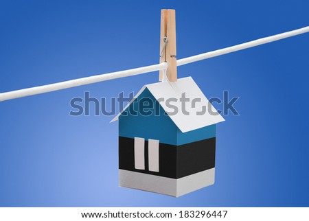 concept - Estonia flag painted on a paper house hanging on a rope - stock photo