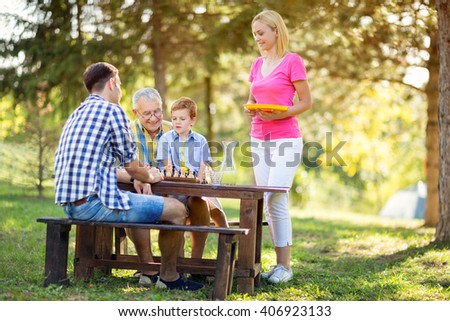 concept family in nature and playing chess - stock photo