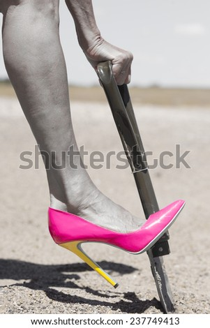 Concept filtered image of female leg wearing pink high heel stiletto shoe and one hand on shovel, digging in remote sandy desert hole in the dirt, blurred background and copy space. - stock photo