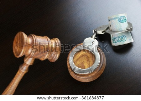 Concept For Corruption, Bankruptcy, Bail, Crime, Bribing, Fraud. Judges Gavel, Handcuffs   And Russian Cash On The Rough Black Wooden Textured Table Background. - stock photo