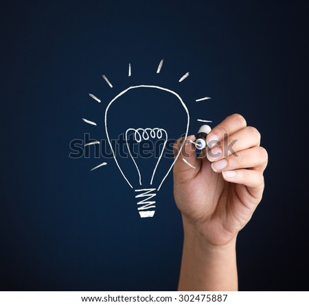 Concept for creative thinking, invention and success. Person drawing a bulb icon with a marker on a blue backdrop - stock photo