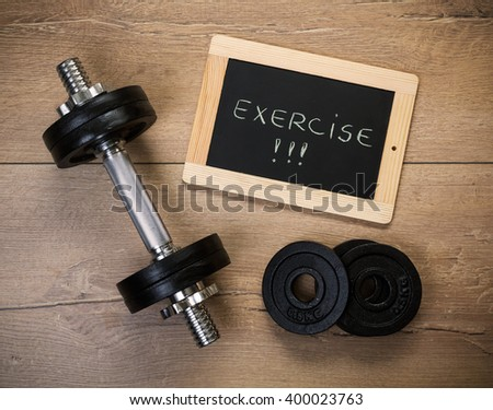 Concept for exercise and sport. Dumbbell and a message on a chalkboard on a wooden background - stock photo