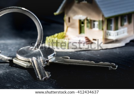 Concept for real estate - House key - Renting Property - Buying a house - Mortgage - Small house background - stock photo