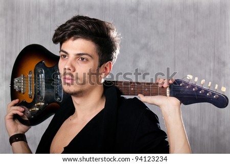 Concept for rock concert. Artistic image of young cool man  with electric guitar. Image taken in studio with backlight and lens flare. - stock photo