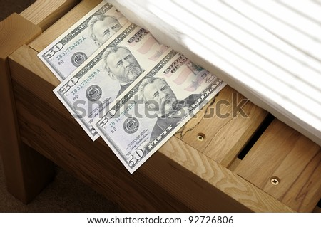 Concept for saving money by stashing it under the mattress. - stock photo