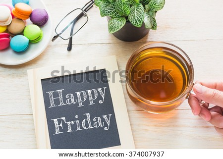 Concept Happy Friday message on wood boards. Macaroons and glass Tea on table. Vintage tone. - stock photo
