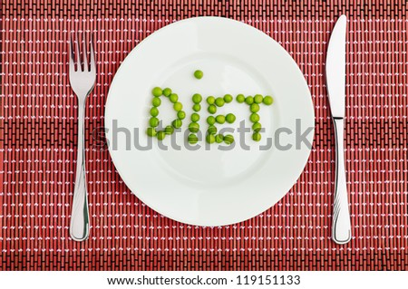 "Concept: healthy  food  and diet. the word ""diet"" green peas on a white plate - stock photo"