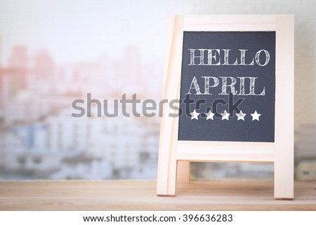 Concept HELLO APRIL message on wood boards - stock photo