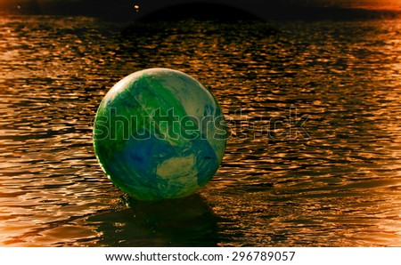 concept image for global environmental issue using inflatable rubber ball with earth like markings and rippled water surface molten metal color - stock photo