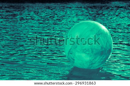 concept image for global environmental issue using inflatable rubber ball with earth like markings and rippled water surface  - stock photo