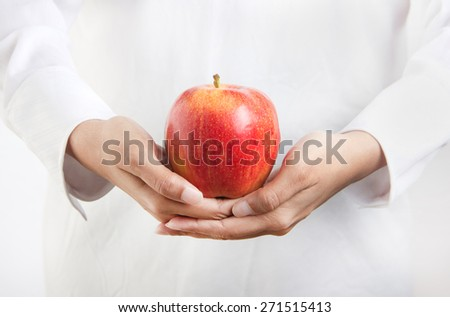 Concept image for healthy diet and lifestyle. Person in white dress is holding a delicious red apple in hand - stock photo
