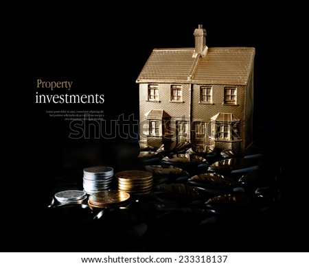 Concept image for property investment. Creatively lit gold house and stacked coins against a black background. Copy space. - stock photo